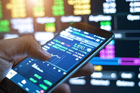 man holding mobile phone studying stocks