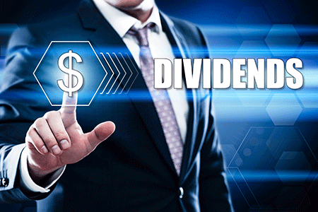 man pointing at a dollar sign with the words dividends and dividend reinvestment plans