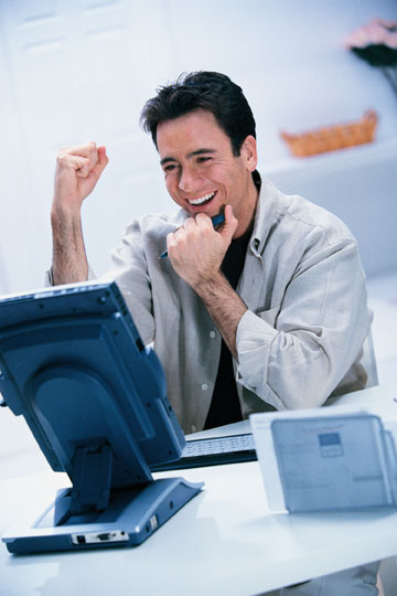 trader in front of a PC with his fist in the air trading to win