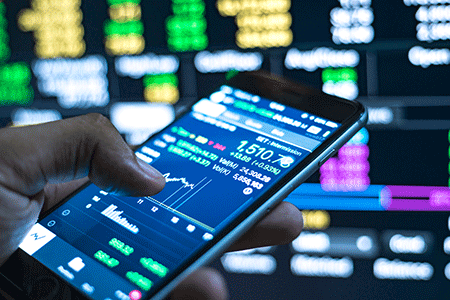 guy holding a phone looking at a stock on the screen